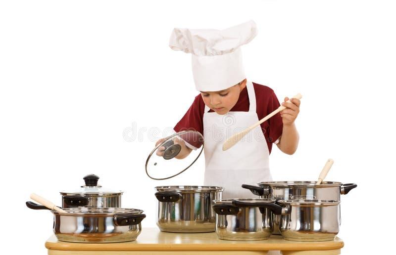 Cozinheiro chefe pequeno que verific o alimento foto de stock royalty free