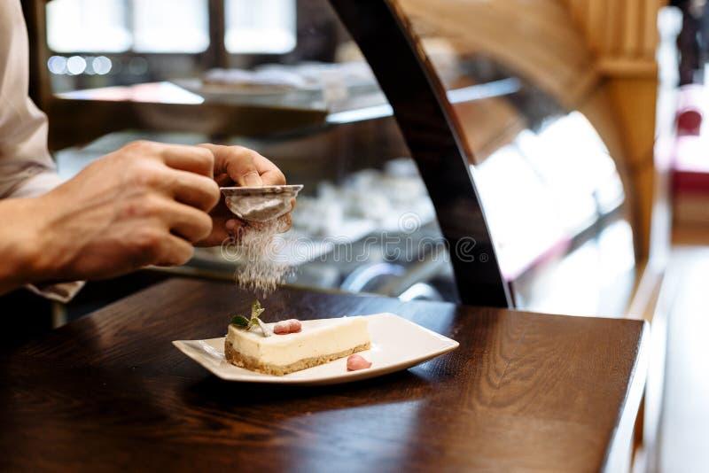 Cozinheiro chefe polvilhado com a peneira do a??car pulverizado de um peda?o de bolo em uma placa em uma tabela de madeira imagens de stock royalty free