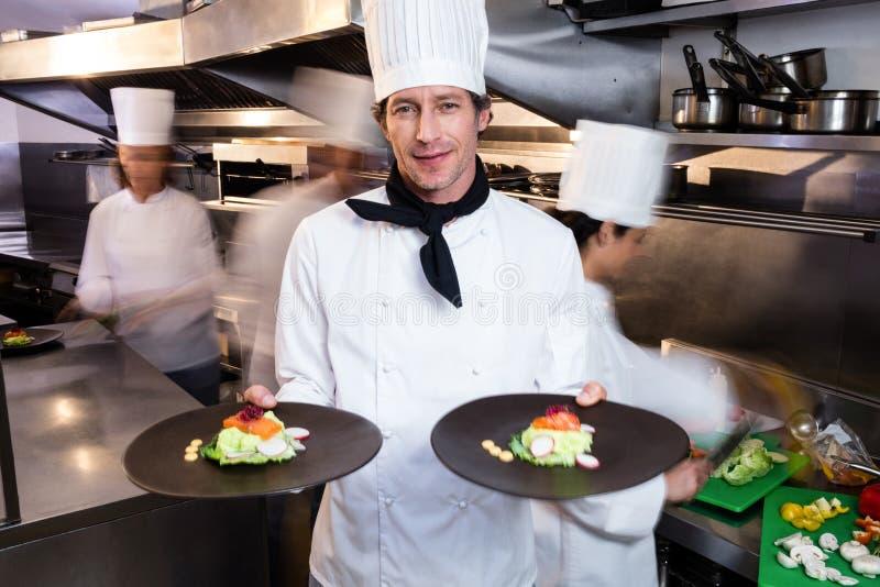 Cozinheiro chefe principal feliz que apresenta suas placas do alimento imagens de stock royalty free