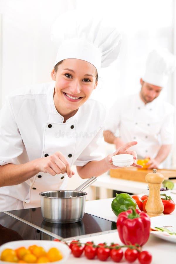 Cozinheiro chefe profissional atrativo novo que cozinha em sua cozinha fotos de stock royalty free