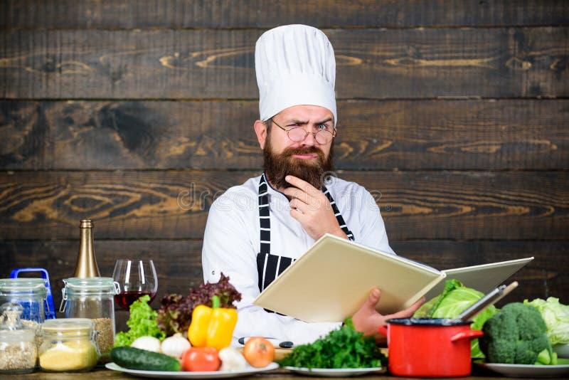 Cozinheiro chefe profissional no uniforme do cozinheiro Homem farpado feliz que cozinha na cozinha Dieta com alimento biológico P fotos de stock