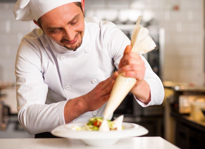 Cozinheiro chefe profissional que decora o prato fotografia de stock