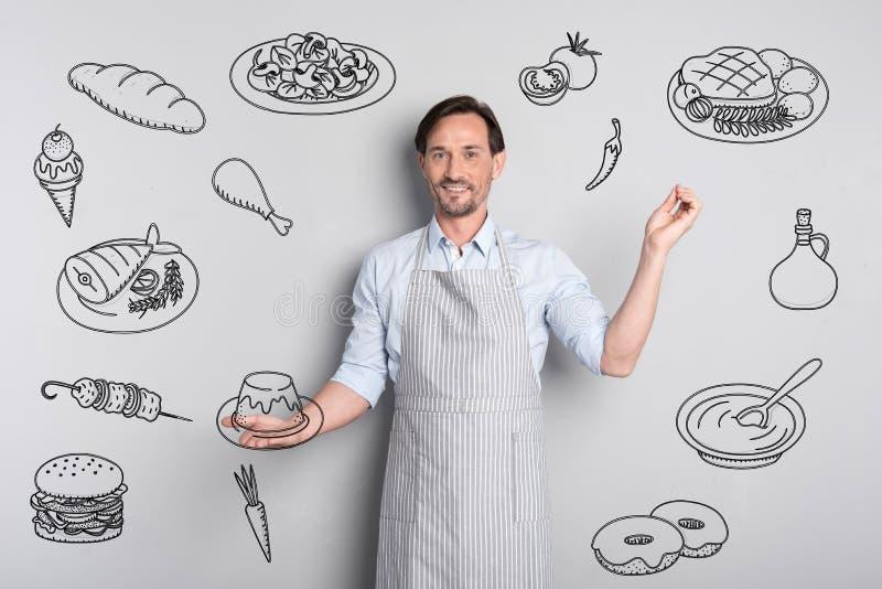 Cozinheiro chefe profissional que sorri ao guardar um pudim saboroso foto de stock royalty free