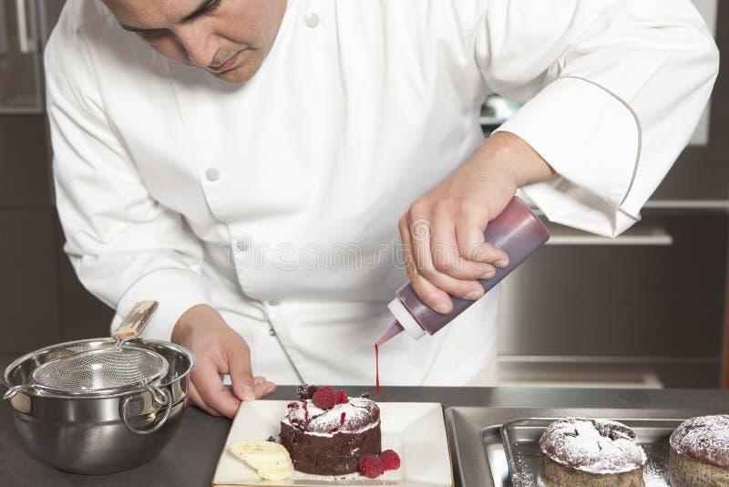 Cozinheiro chefe Puts Finishing Touches no bolo de chocolate no contador de cozinha fotografia de stock
