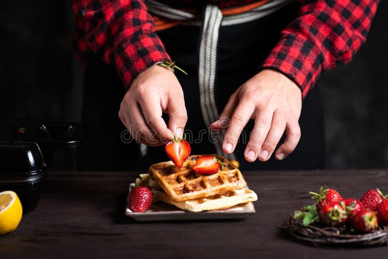 Cozinheiro chefe que adiciona morangos em um fim do waffle acima foto de stock royalty free