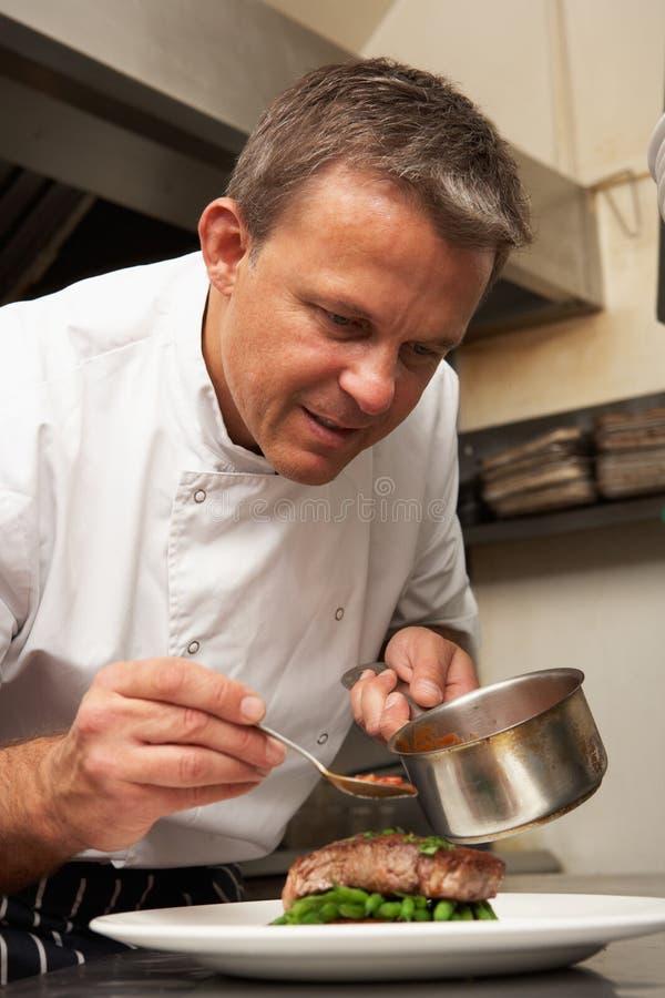 Cozinheiro chefe que adiciona o molho ao prato no restaurante fotografia de stock