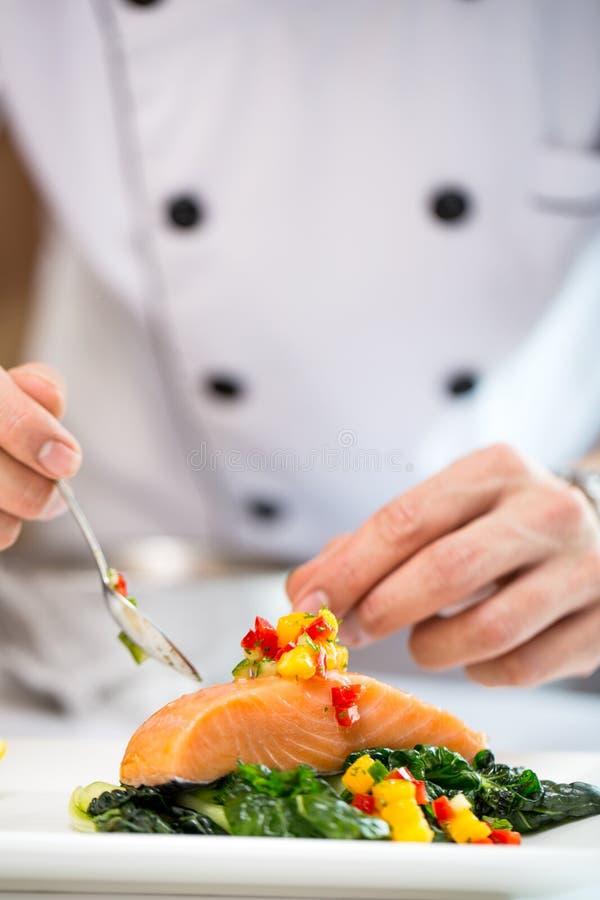 Cozinheiro chefe que ajusta fresco delicioso fotografia de stock