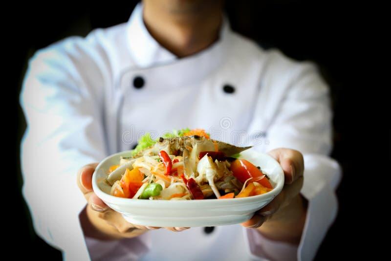 Cozinheiro chefe que apresenta orgulhosamente a salada picante tailandesa da papaia do caranguejo - Lao, culinária de Isan foto de stock royalty free