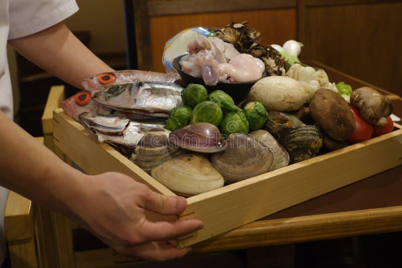 Cozinheiro chefe que apresenta a receita culinária fresca vegetal do marisco dos peixes do ingrediente de alimento fotografia de stock
