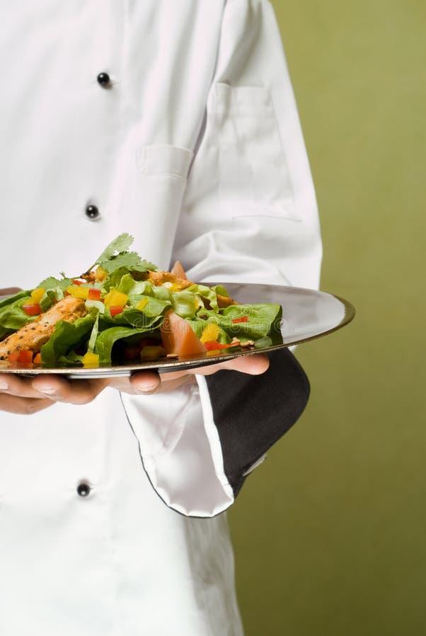 Cozinheiro chefe que apresenta a salada saudável da galinha foto de stock