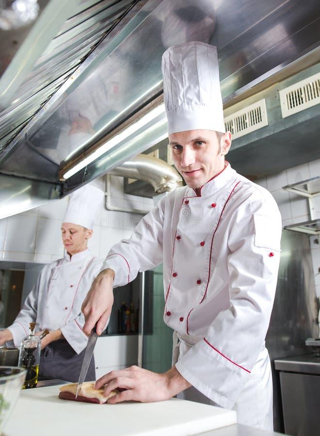 Cozinheiro chefe que corta a carne na placa de desbastamento, faca profissional da terra arrendada do cozinheiro e cortando a car fotos de stock royalty free