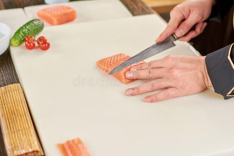 Cozinheiro chefe que corta a faixa salmon fresca crua imagens de stock