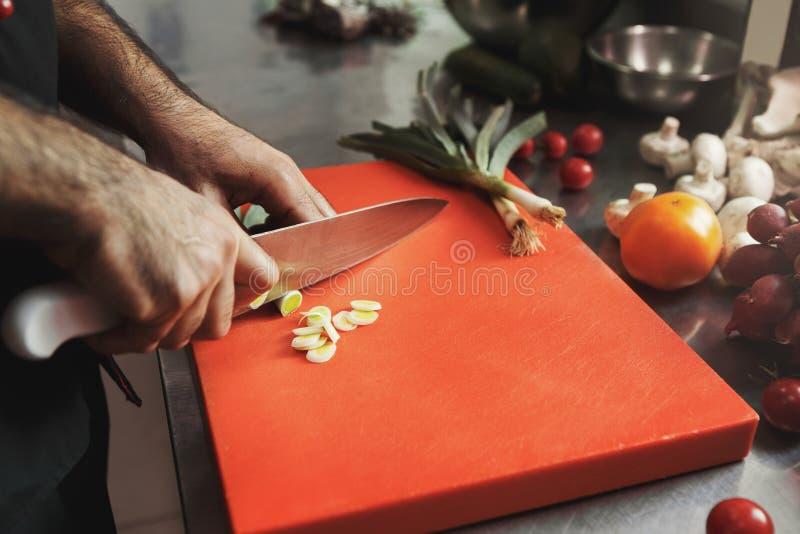 Cozinheiro chefe que corta legumes frescos para a salada foto de stock royalty free