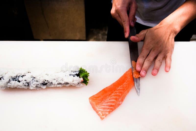 Cozinheiro chefe que corta o sashimi salmon fresco fotos de stock