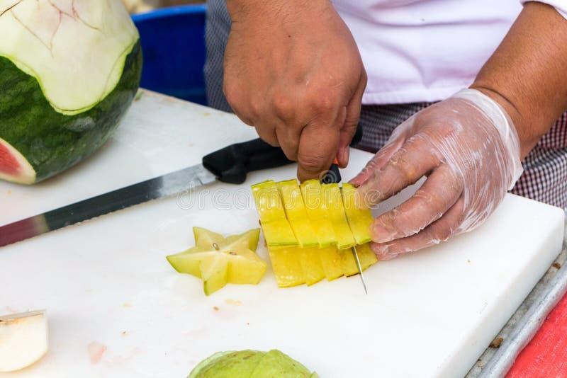 Cozinheiro chefe que corta o starfruit imagem de stock