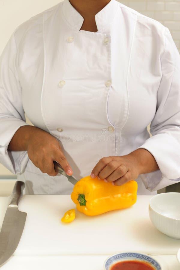 Cozinheiro chefe que corta a pimenta amarela imagens de stock