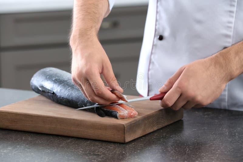 Cozinheiro chefe que corta salmões frescos imagens de stock royalty free