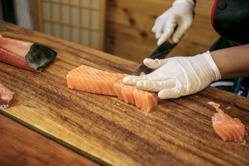 Cozinheiro chefe que corta salmões frescos foto de stock