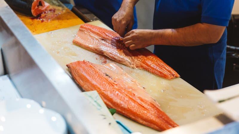Cozinheiro chefe que corta salmões frescos e para remover os ossos da barriga da faixa pelas mãos para fazer o sushi e o sashimi  fotografia de stock