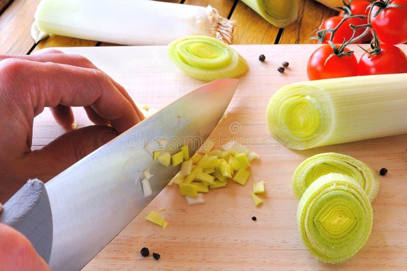 Cozinheiro chefe que corta um alho-porro na placa de corte imagens de stock royalty free