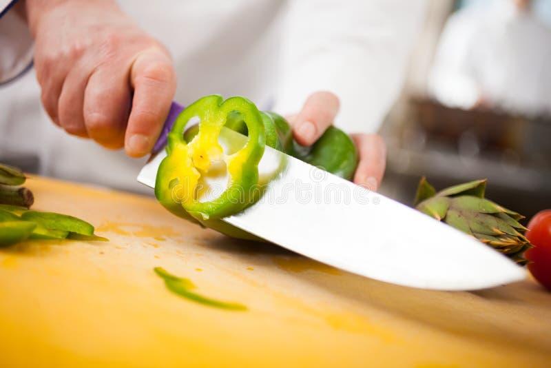 Cozinheiro chefe que corta uma pimenta verde fotografia de stock royalty free