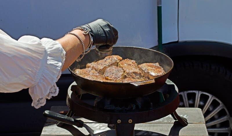 Cozinheiro chefe que cozinha a carne grelhada fotografia de stock royalty free