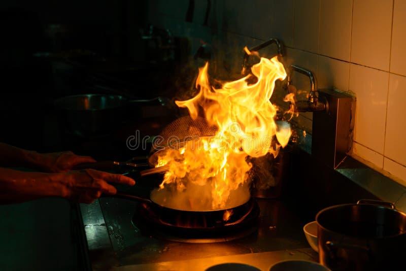Cozinheiro chefe que cozinha e que faz o flambe no alimento na cozinha foto de stock royalty free