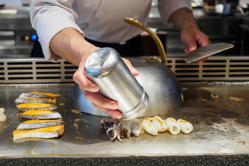 Cozinheiro chefe que cozinha e que polvilha especiarias no marisco no restaurante do teppanyaki fotografia de stock