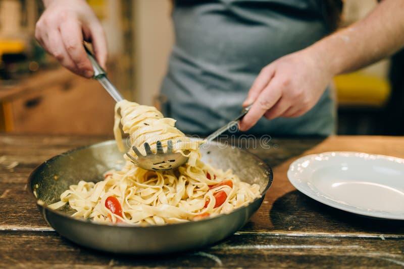 Cozinheiro chefe que cozinha a massa, bandeja na mesa de cozinha de madeira imagens de stock royalty free