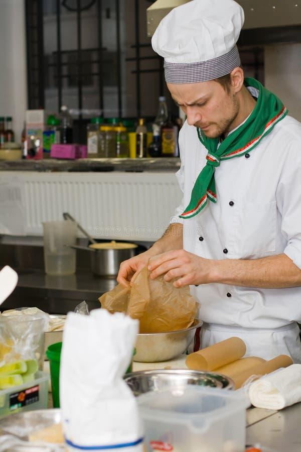 Cozinheiro chefe que cozinha na cozinha fotos de stock royalty free