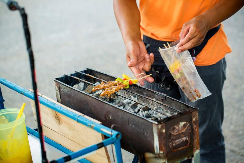 cozinheiro chefe que cozinha no bufete do jantar do assado Alimento da rua da grade do assado em Tailândia foto de stock