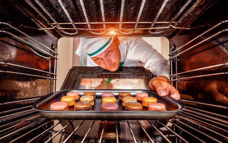 Cozinheiro chefe que cozinha no forno imagem de stock royalty free