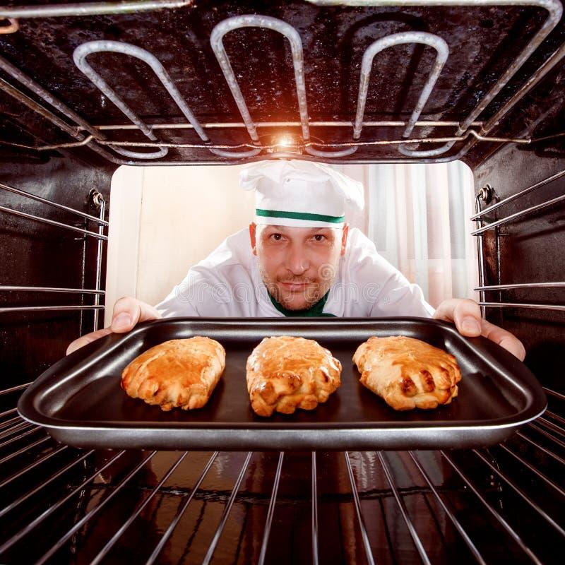 Cozinheiro chefe que cozinha no forno foto de stock royalty free