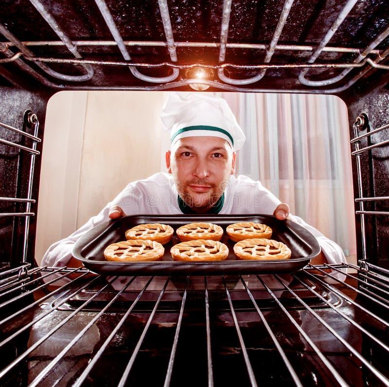 Cozinheiro chefe que cozinha no forno fotografia de stock
