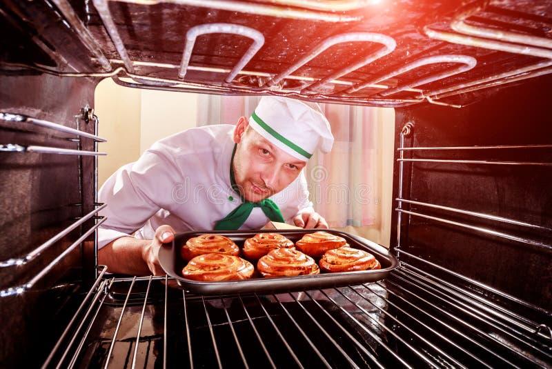 Cozinheiro chefe que cozinha no forno fotografia de stock royalty free