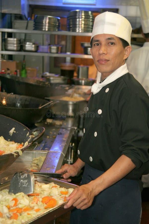 Cozinheiro chefe que cozinha no restaurante da cozinha foto de stock