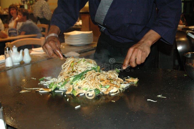 Cozinheiro chefe que cozinha o japonês foto de stock