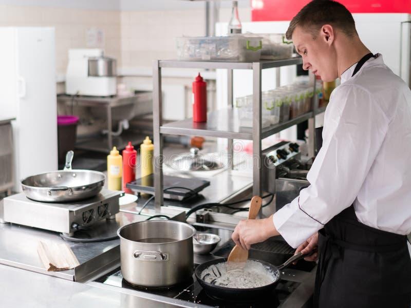 Cozinheiro chefe que cozinha o trabalho profissional da cozinha do restaurante fotos de stock