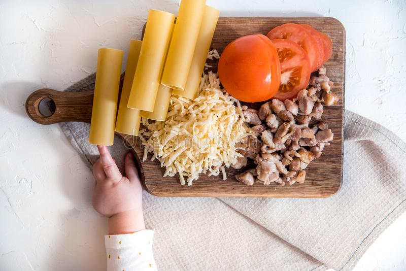 Cozinheiro chefe que cozinha os espaguetes na cozinha cozinhando o cannelloni da massa massa e molho béchamel crus em um fundo br fotografia de stock