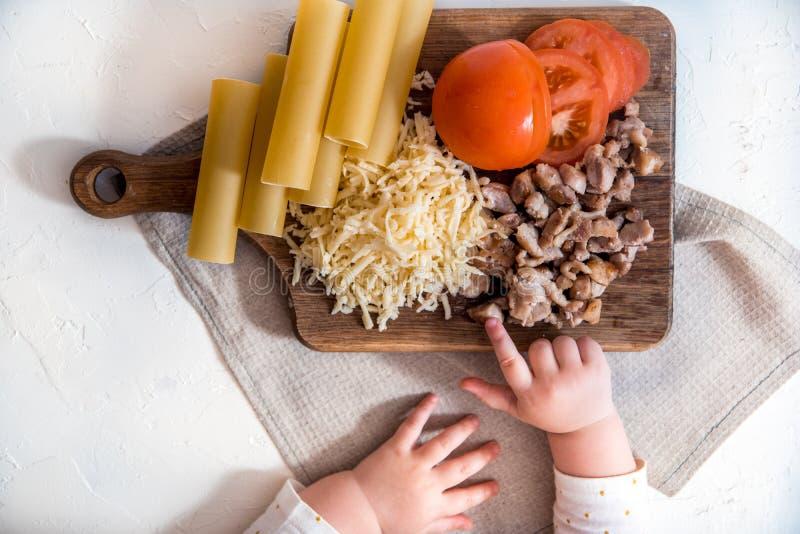Cozinheiro chefe que cozinha os espaguetes na cozinha cozinhando o cannelloni da massa massa e molho béchamel crus em um fundo br foto de stock