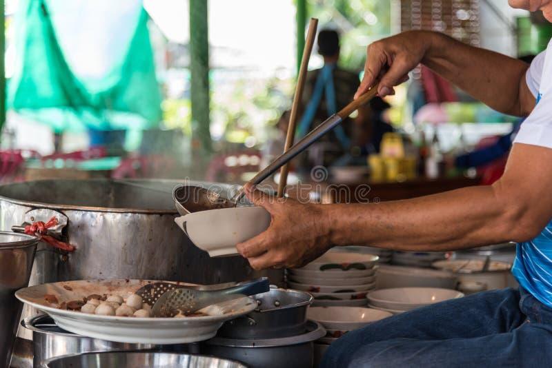Cozinheiro chefe que cozinha uma sopa de macarronete no mercado do alimento da rua imagem de stock royalty free