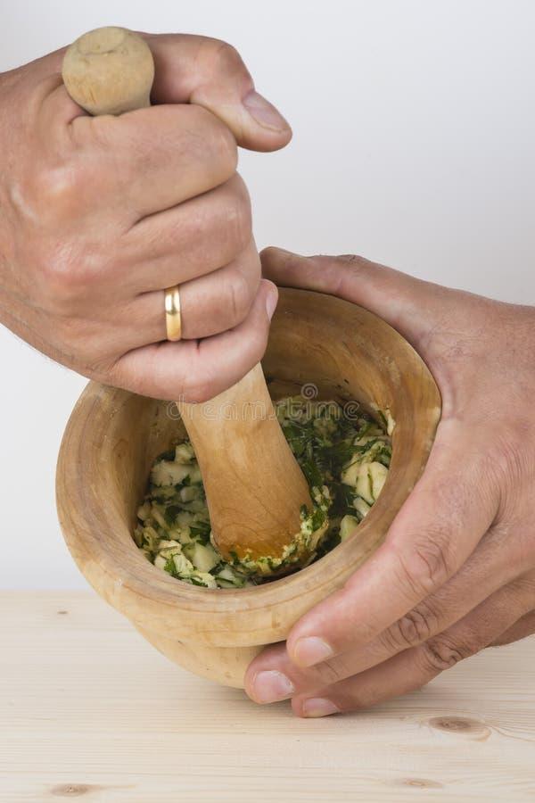 Cozinheiro chefe que esmaga o alho e a salsa com almofariz e pilão no k fotos de stock royalty free