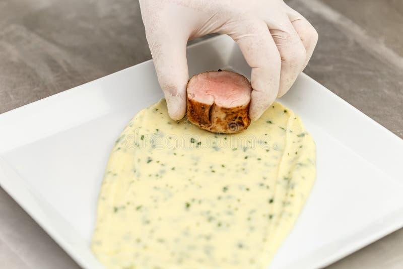 Cozinheiro chefe que faz o prato da carne foto de stock royalty free