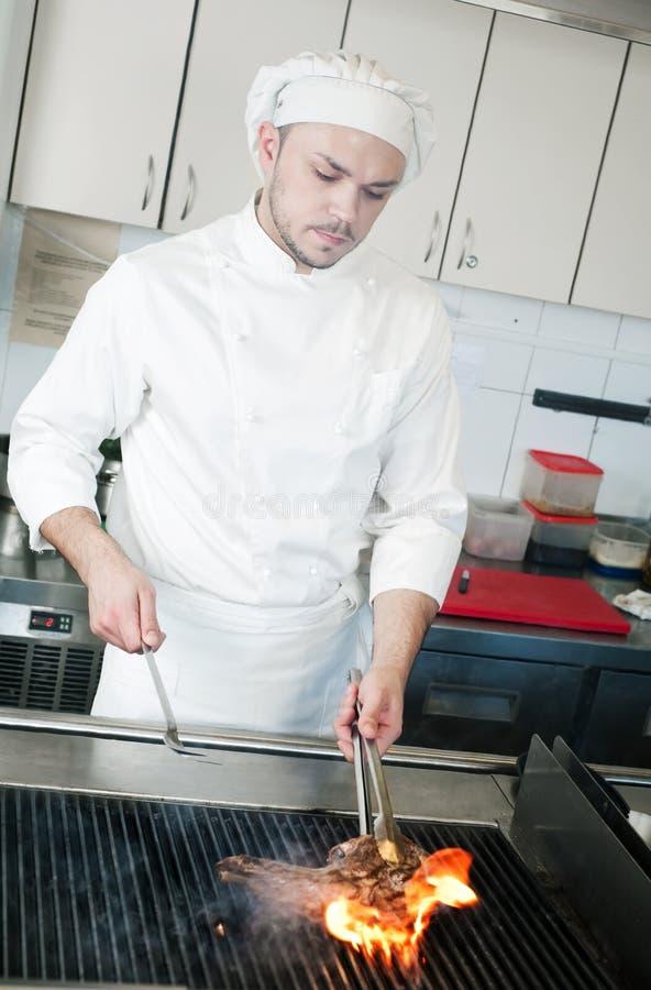 Cozinheiro chefe que frita o bife de carne na grade fotografia de stock
