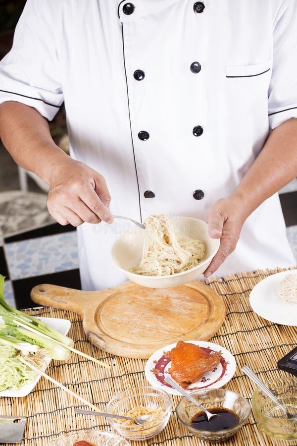 Cozinheiro chefe que guarda o macarronete da bacia com forquilha foto de stock