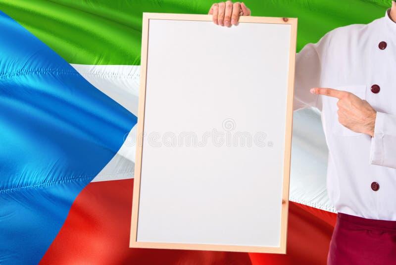 Cozinheiro chefe que guarda o menu vazio do whiteboard no fundo da bandeira da Guiné Equatorial Cozinhe o uniforme vestindo que a fotos de stock