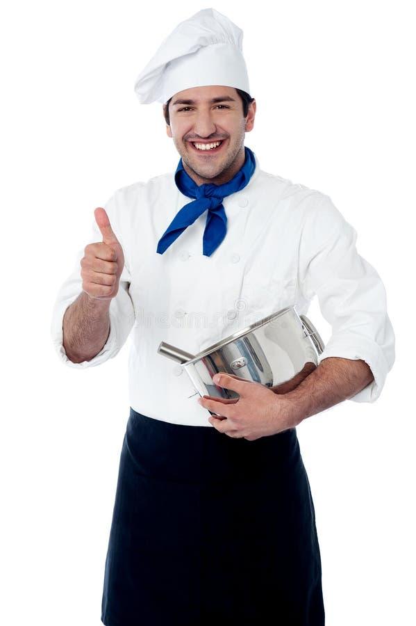 Cozinheiro chefe que guarda um potenciômetro que mostra o sinal aprovado da mão imagem de stock royalty free