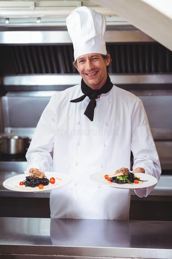 Cozinheiro chefe que mostra placas dos espaguetes imagem de stock