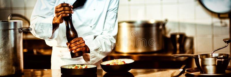 Cozinheiro chefe que polvilha a pimenta em uma refeição imagem de stock