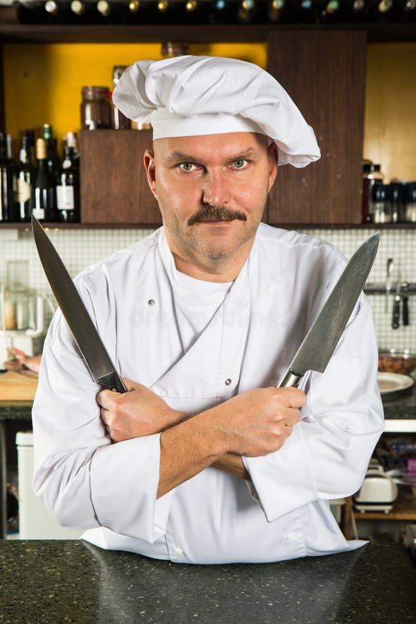 Cozinheiro chefe que prende duas facas imagens de stock royalty free